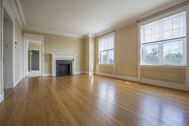 Spacious Central West End living room with large windows and fireplace