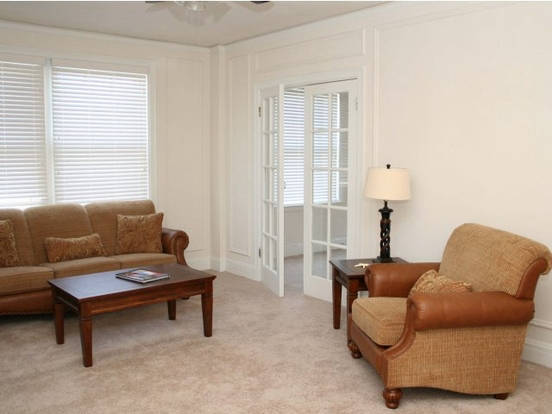 Bright Embassy living room with carpeted floors & french doors