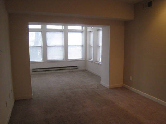 Spacious Waterman Clara living room with carpeted floors and oversized windows