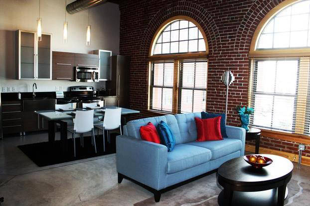 Ballpark Loft living space with huge decorative windows and exposed brick walls