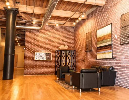 Open floor plan with exposed brick wall in a Bogen Lofts living room