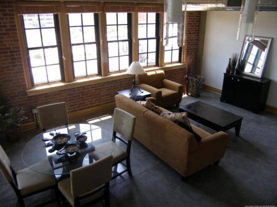 Spacious GW Loft living and dining space with large windows and industrial style brick
