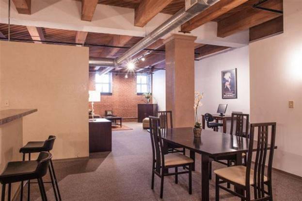 Spacious Vangard Loft living space with exposed beams an concrete floors