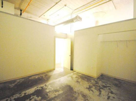 Industrial-style 1818 Washington Avenue bedroom with polished concrete floors and large closet